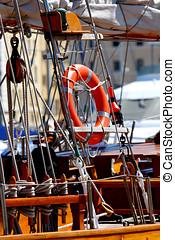 Lifebelt - a lifebuoy on a sailboat mast behind ropes