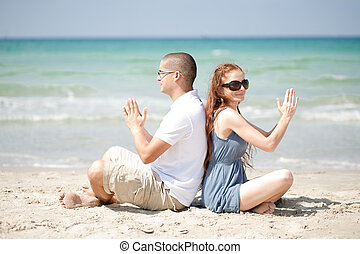 Couple doing exercises on the beach sand