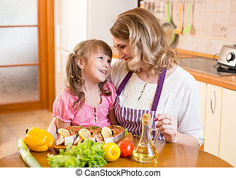 mother and kid cook and communicate in kitchen