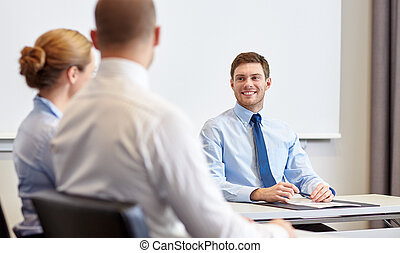 group of smiling businesspeople meeting in office -...