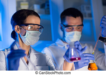 close up of scientists making test in lab - science,...