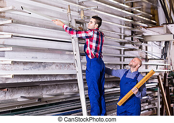 Workers searching for profiles on rack - Workers on a...
