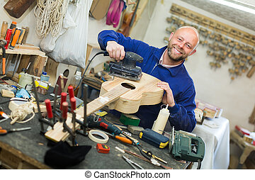 Man working on a machine at guitar workshop - Positive...