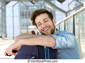 Cheerful young man relaxing at station with bag - Portrait...