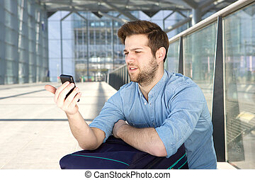 Man looking at mobile phone with confused expression -...