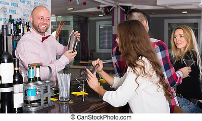 Friends drinking and chatting with smiling barman at bar...