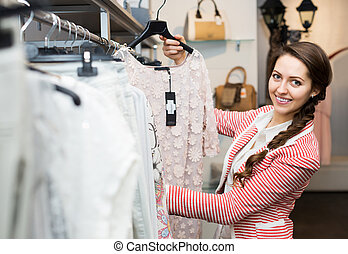 Attractive woman renewing her wardrobe - Apparel shop:...