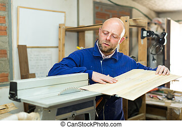 Man working on a machine at wood workshop - Portrait of...