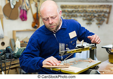 Woodworker on lathe in workroom - Portrait of adult...