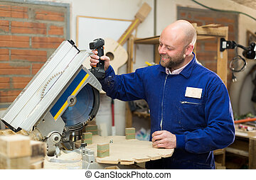 Professional carpenter using power-saw - Smiling...