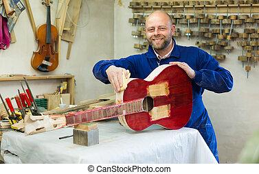 Guitar-maker at workshop - Joyful guitar-maker working with...