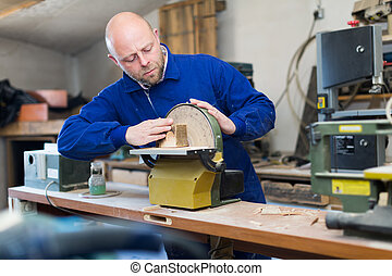 Man working on a machine at guitar workshop - Skilled...