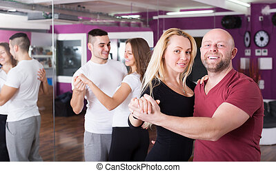 Couples enjoying of partner dance - Cheerful adult couples...