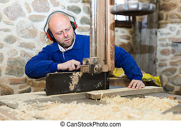 Man working on a machine at wood workshop - Serious...