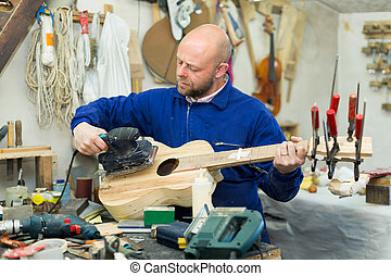 Man working on a machine at guitar workshop - Serious...
