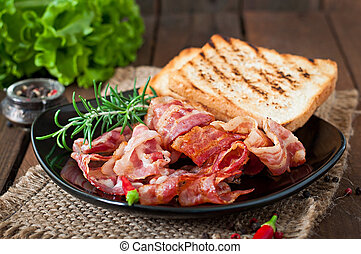 Fried bacon and toast on a black plate on a wooden...