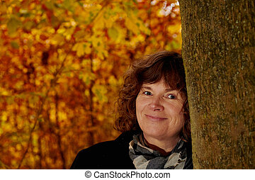 Fall - mugshot of mature woman looking at you - Autumn -...