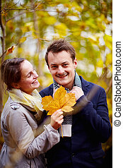 Fall - Cute young couple holding maple leaf in forest