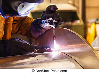 Man welding - Young man with protective mask welding in a...