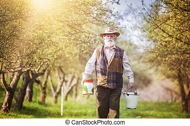 Farmer with milk bottles - Senior farmer with jug and bucket...