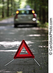 broken down car with warning triangle behind it waiting for...