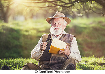Farmer with cheese - Senior farmer cutting and eating cheese...
