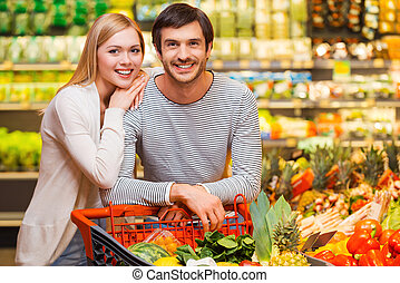 Shopping together for dinner. Cheerful young couple smiling...