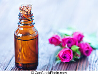rose oil in bottle and on a table