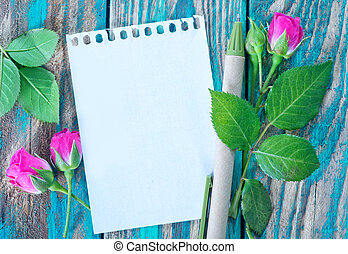 rose and note on the wooden table