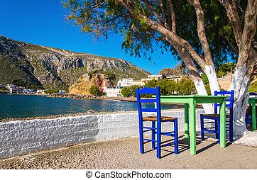 Green table, chairs in romantic Greek bay, Greece