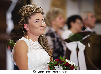 Beautiful bride during a mass in the church