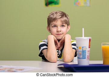 Lunch break in classroom - Little boy having lunch break in...
