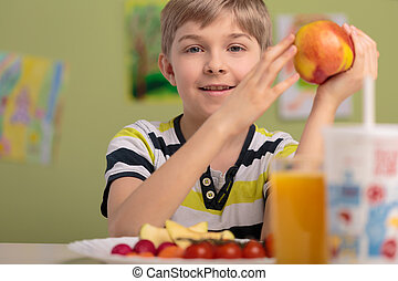 Boy eating fruits for lunch - Happy boy eating fresh fruits...