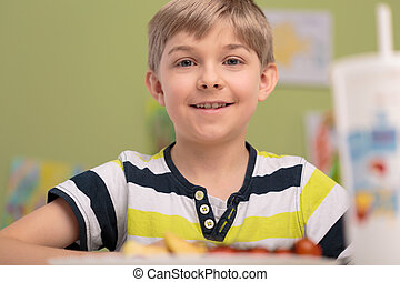 Boy eating breakfast in classroom - Happy smiling boy eating...