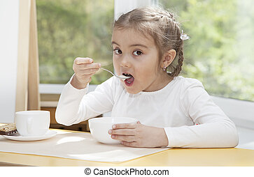 Little child eats yogurt - Little blonde preschooler girl...
