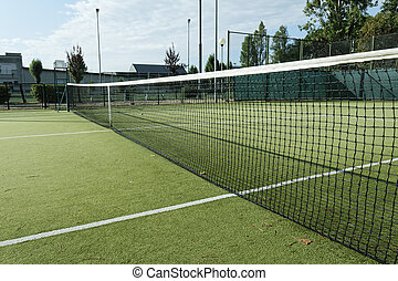 green tennis court in the town of la spezia