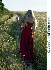 Beautiful blond woman back on a path in a wheat field