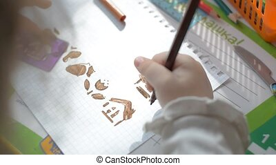 Child draws using a stencil - Child draws on the table brown...