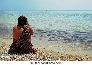girl sitting on the seashore and watching horizon