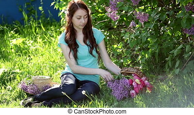 beautiful woman with a bouquet of lilac sitting in the...