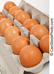 Brown whole eggs in a carton