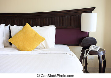 Bed, pillows and lamp in the hotel room