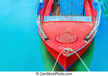 Empty red wooden boat with blue broadside moored in port...