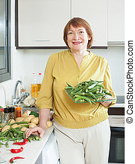 mature woman with okra in kitchen - Positive mature woman...