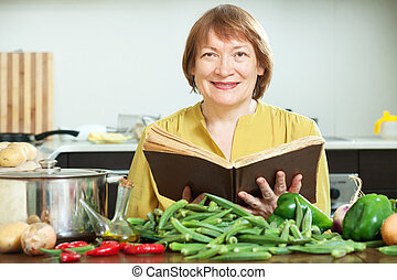 Smiling mature woman cooking with  cookery book