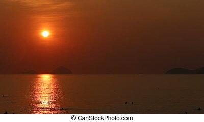 people swim in sea at sunrise against small islands -...