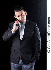 young asian business man talking on mobile phone against...