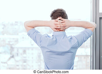 Businessman standing with hands behind his head - Time to...