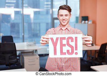 Office worker holding poster with yes slogan - Say yes Young...
