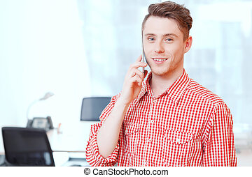 Young handsome office manager talking per mobile phone.
